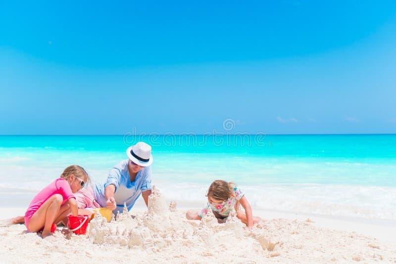 做沙子的父亲和小女儿防御在热带海滩 免版税库存照片