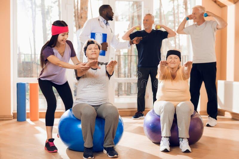 做治疗体操的一个小组年长妇女和人在老人院 免版税图库摄影