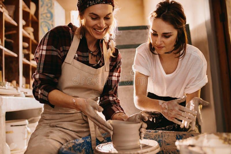 做泥罐的瓦器车间的两名妇女 库存照片