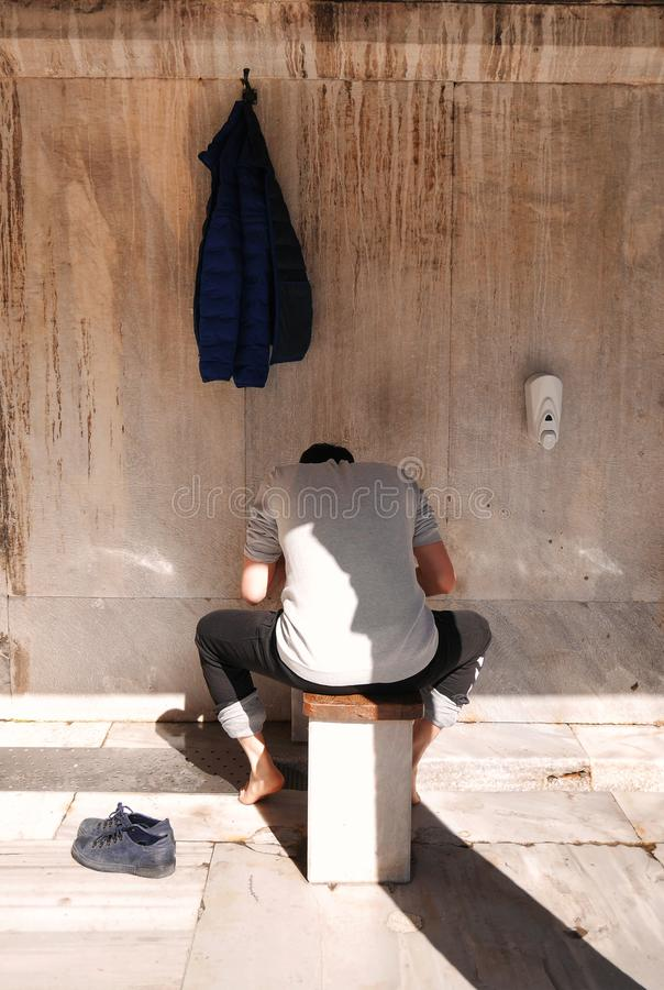 做洗手、嘴、鼻孔、胳膊、头和脚用水武都的洗净液过程的回教信徒 图库摄影