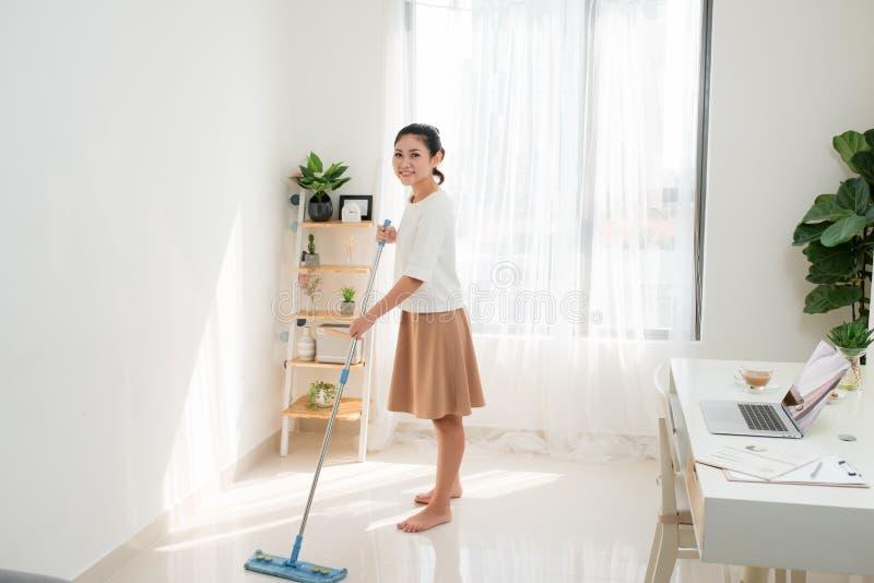 做清洁的年轻亚裔妇女在家庭办公室 免版税库存照片