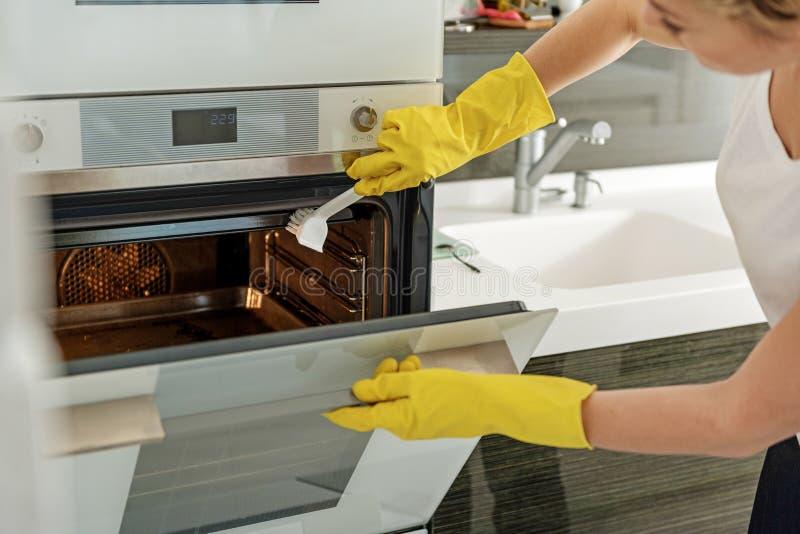 做清洁的仔细的主妇在厨房 免版税库存照片