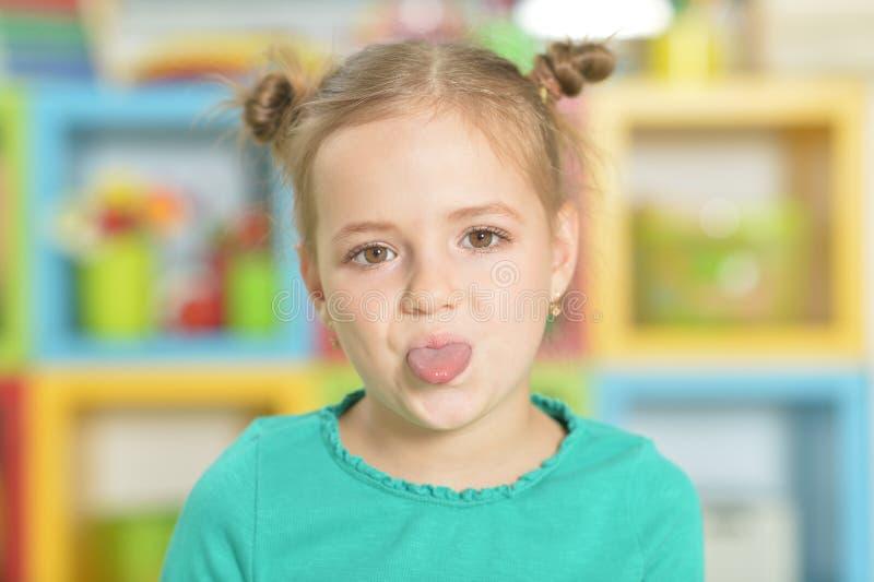 做滑稽的面孔的一个小女孩的画象 免版税库存照片