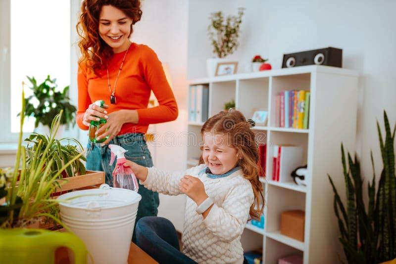 做滑稽的面孔的快乐的女孩在洒水以后在家庭植物 免版税图库摄影