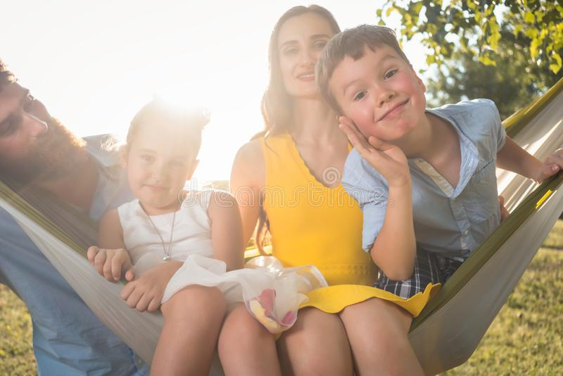 做滑稽的面孔的逗人喜爱的孩子,当看照相机为家庭画象时 免版税图库摄影