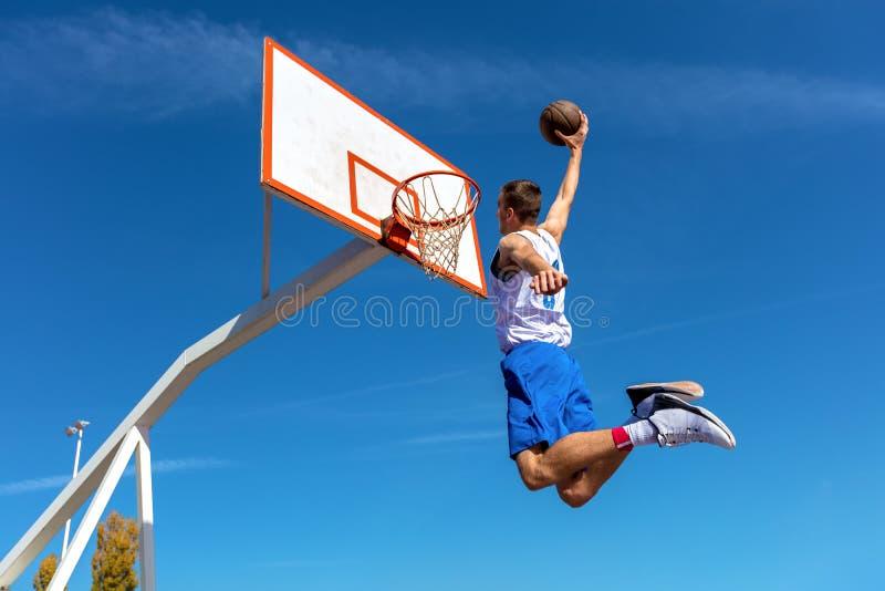 做灌篮的年轻篮球街道球员 免版税库存照片