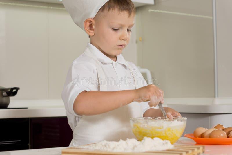 做烘烤的逗人喜爱的年轻男孩 免版税库存图片