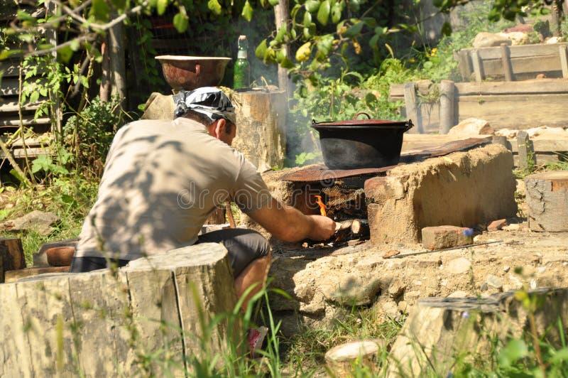 做烹调的年轻人火外面 免版税库存图片