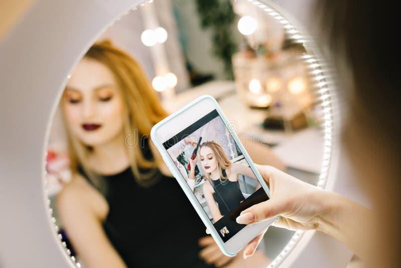 做照片的典雅的俏丽的年轻女人在镜子的电话在做在美发师沙龙的发型期间 ?? 图库摄影