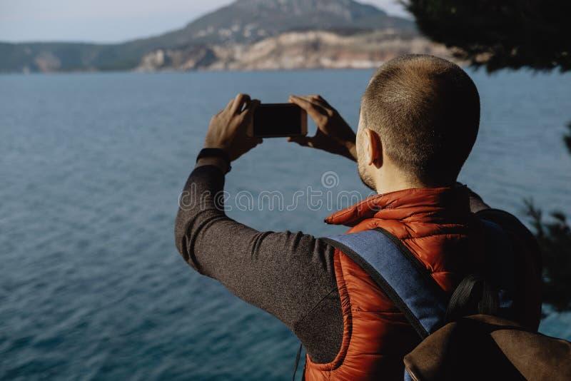 做照片的后面观点的年轻男性旅客由在bac的电话 免版税图库摄影