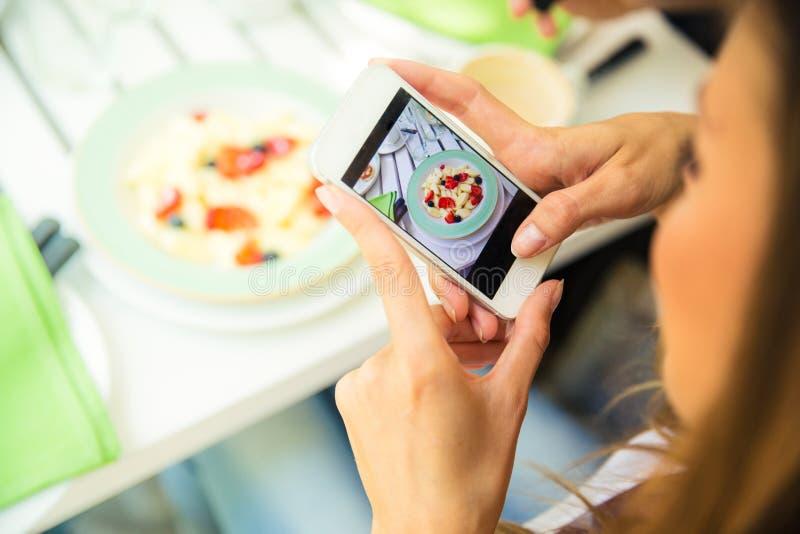 做照片的妇女食物在智能手机 免版税库存图片