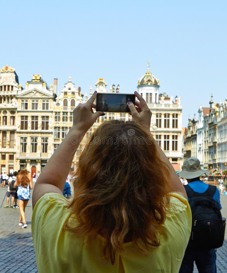 做照片的年轻女人布鲁塞尔大广场在布鲁塞尔,比利时 免版税库存图片