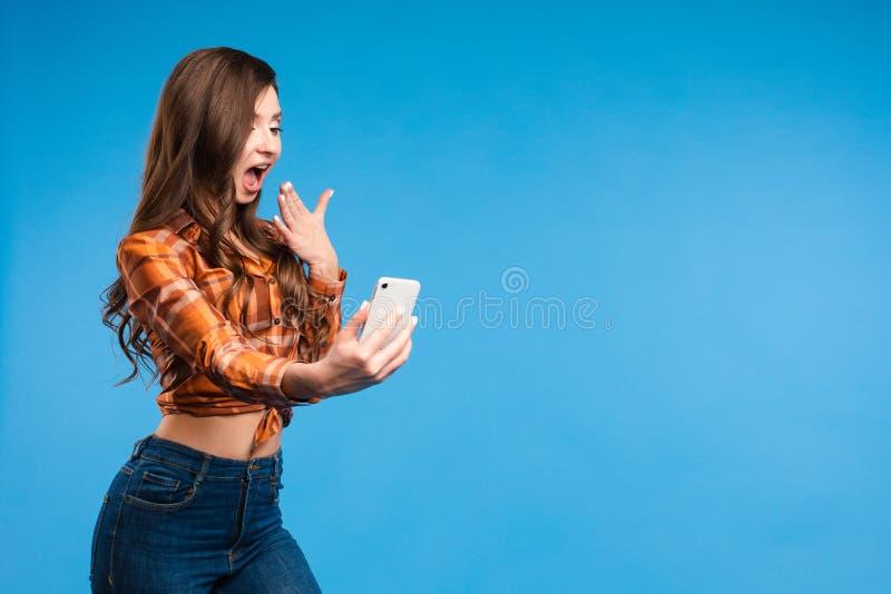 做照片的年轻引诱的女孩她是站立和采取与smartphon的selfie 免版税图库摄影