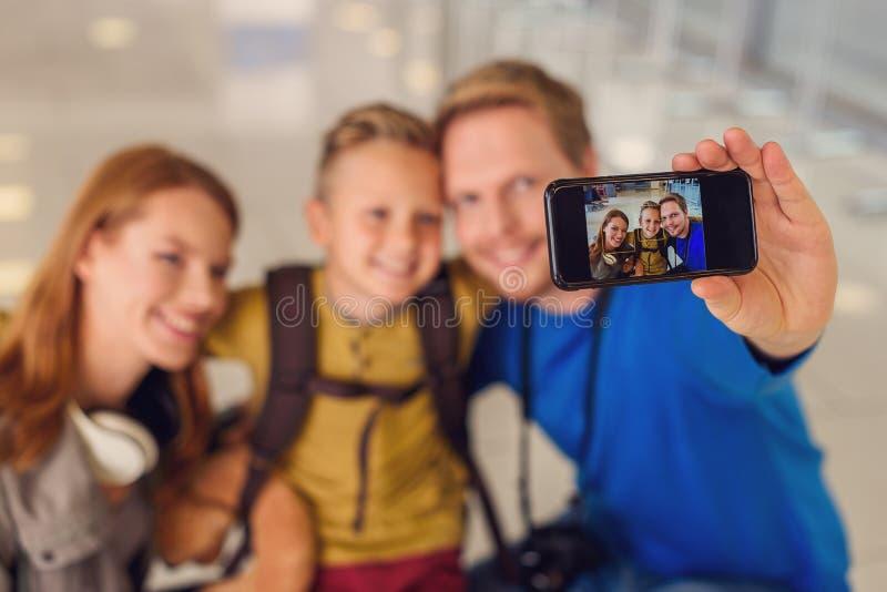 做照片的愉快的家庭在机场 免版税库存图片