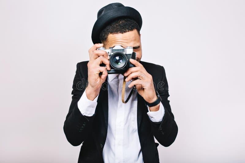 做照片的衣服的画象激动的帅哥在白色背景的照相机 获得乐趣,享受旅行,游人 免版税图库摄影