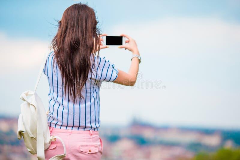做照片的年轻白种人妇女欧洲老城市由手机由观察地方 免版税库存图片