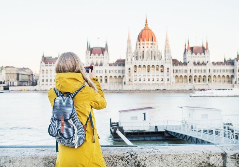 做照片的年轻blondy妇女游人与她的电话的议会历史建筑在布达佩斯,匈牙利 库存图片