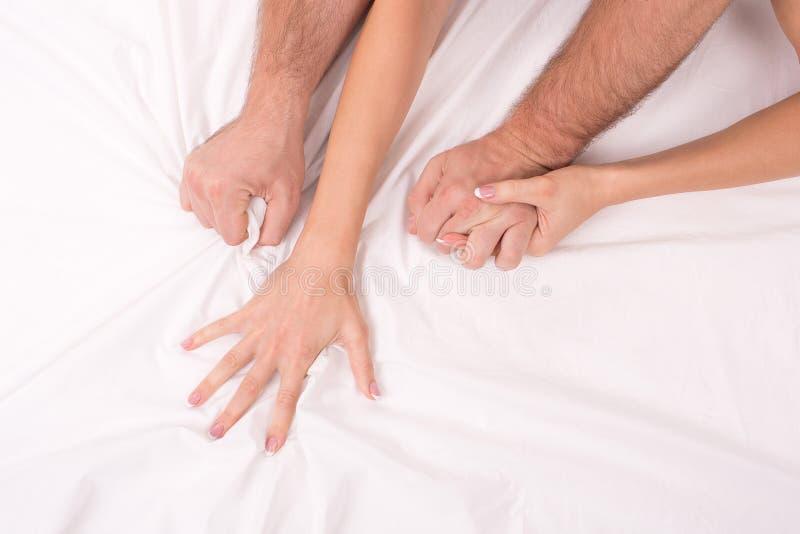 做爱在床上在白色弄皱板料夫妇,在手上的焦点的手 图库摄影