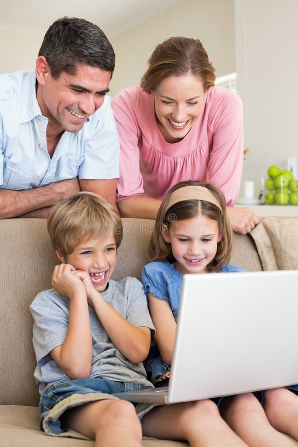 做父母使用膝上型计算机的观看的孩子 免版税库存图片