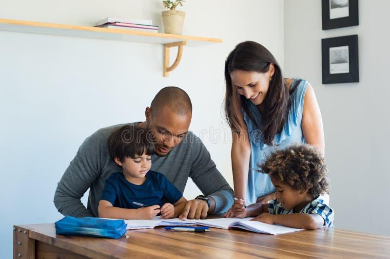 做父母有家庭作业的帮助的孩子 库存图片