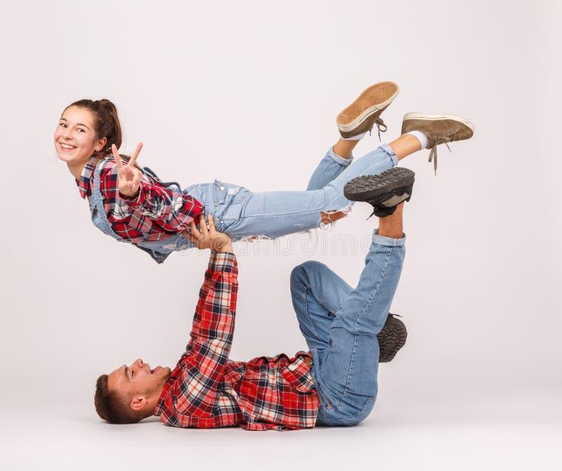 做特技动作的一对年轻愉快的夫妇 背景查出的白色 免版税图库摄影