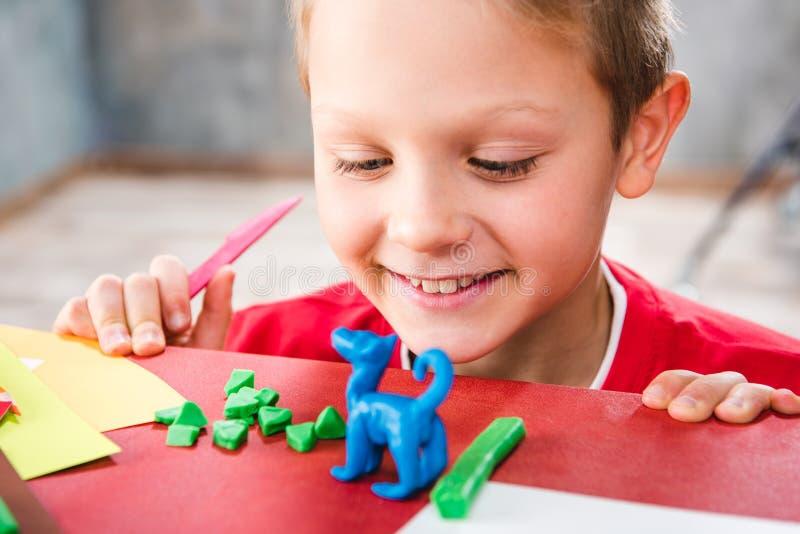 做玩具的学童由彩色塑泥 库存照片