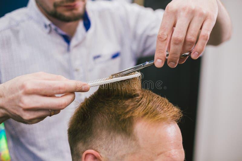 做理发有胡子的人的理发师在理发店 在沙龙的专业美发师切口客户头发 理发师使用 免版税库存图片