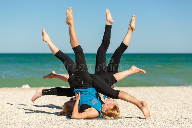 做瑜伽健身的四名妇女在海海滩行使 免版税库存照片