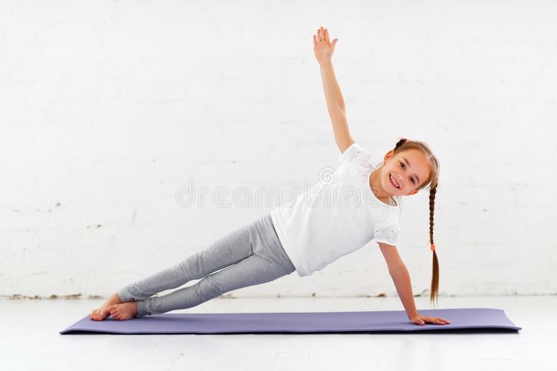 做瑜伽和体操在健身房的儿童女孩 库存图片