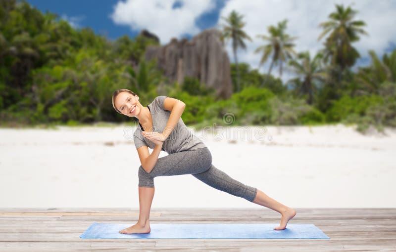 做瑜伽在海滩的妇女侧角姿势 库存图片