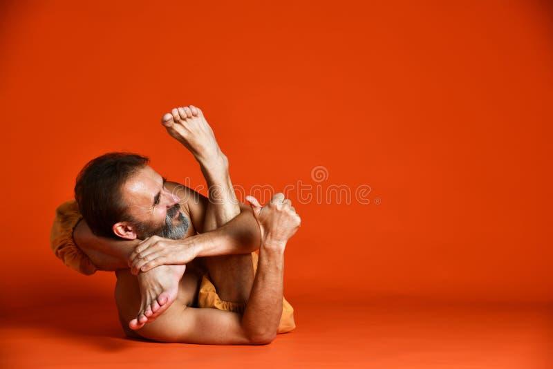 做瑜伽姿势和舒展他的腿的资深有胡子的人演播室射击赤裸上身 免版税库存图片