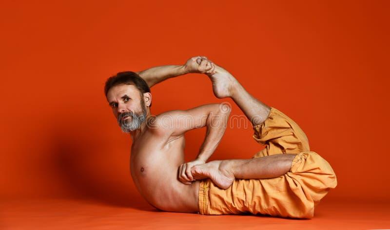 做瑜伽姿势和舒展他的腿的资深有胡子的人演播室射击赤裸上身 图库摄影