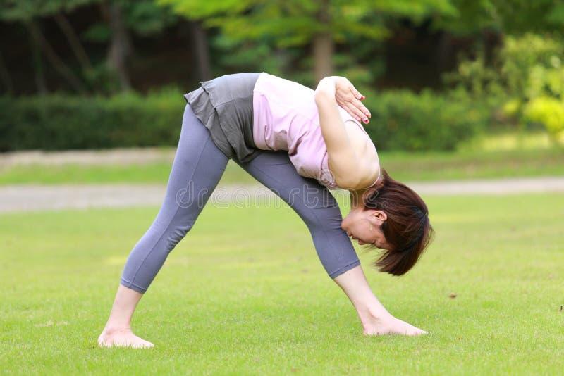 做瑜伽强烈的旁边舒展姿势的日本妇女 库存照片
