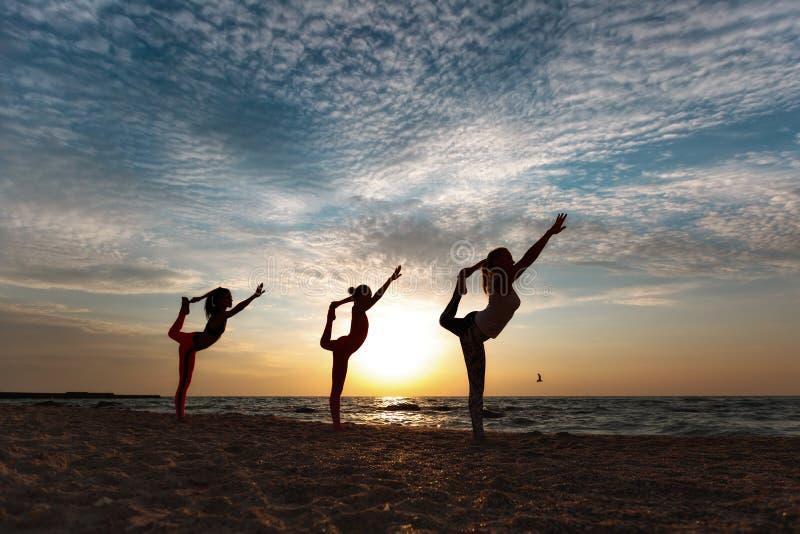 做瑜伽的一个小组妇女在日出在海附近 免版税库存照片