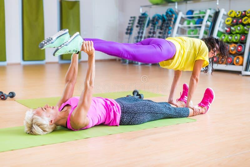 做瑜伽的两个女性健身模型在行使,说谎在地板席子的一个握别的腿在她上体育 免版税库存照片