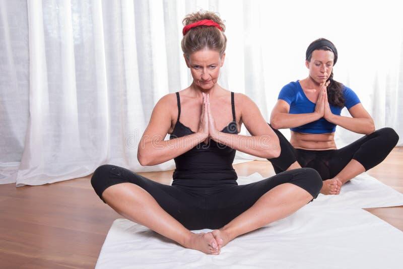 做瑜伽的两名可爱的妇女 免版税图库摄影