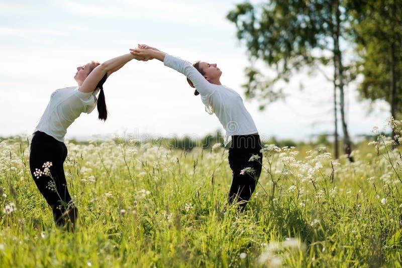 做瑜伽的两名妇女le在自然公园行使,站立互相弯曲在户外 免版税库存照片