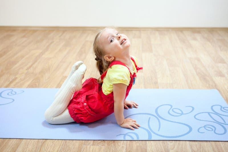 做瑜伽的俏丽的女孩在健身房的席子摆在 免版税库存图片