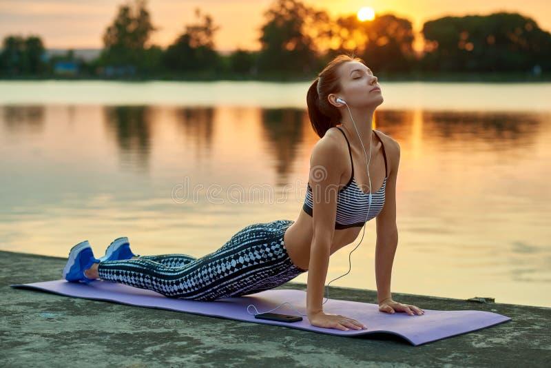 做瑜伽的俏丽的女孩行使白色夏天日落 库存图片