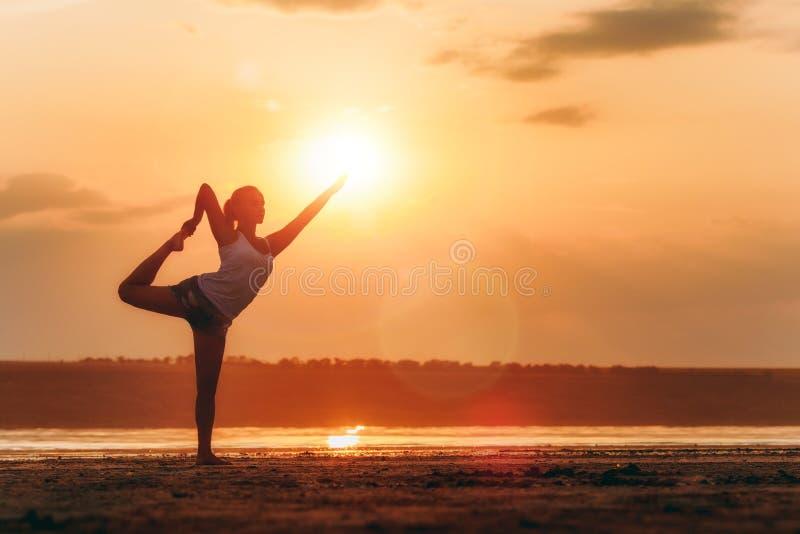做瑜伽的俏丽的妇女在日落户外 免版税库存照片