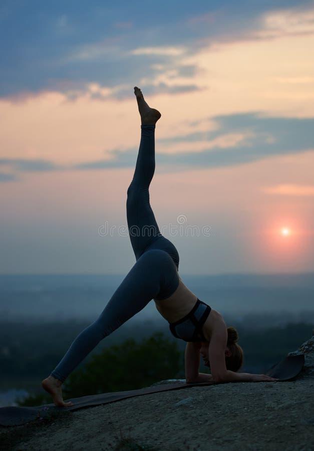 做瑜伽的可爱的亭亭玉立的少妇在美丽的天空背景行使户外  库存照片