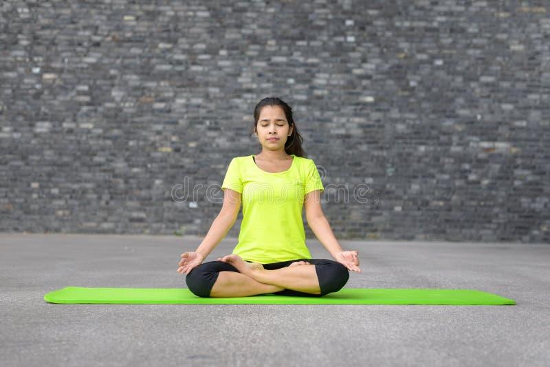 做瑜伽的可爱的精神少妇 免版税库存照片