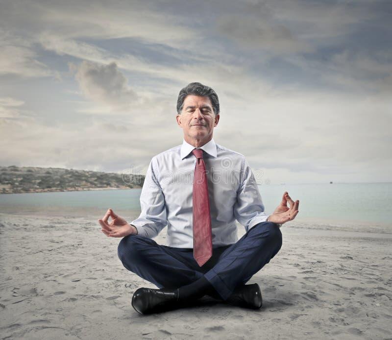 做瑜伽的商人在海边 图库摄影