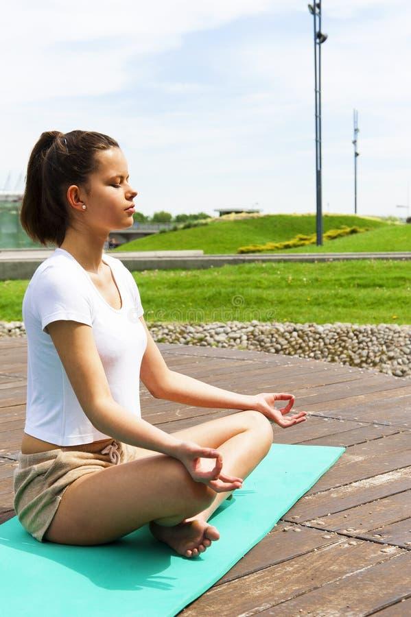 做瑜伽的女孩在公园 在草 免版税库存照片