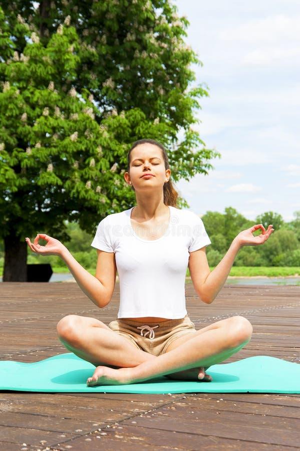 做瑜伽的女孩在公园 Lotos位置 免版税库存照片