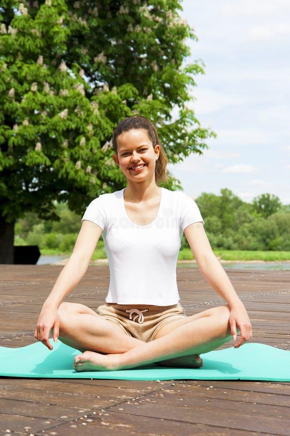 做瑜伽的女孩在有大微笑的公园 库存图片