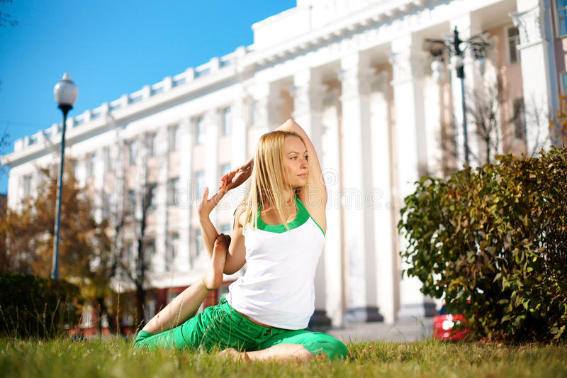 做瑜伽的女孩户外在公园 免版税库存照片