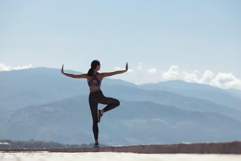 做瑜伽的女孩早晨,在江边由海 库存照片