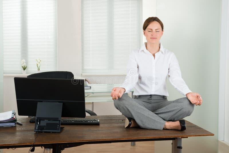 做瑜伽的女实业家在办公室 免版税库存照片