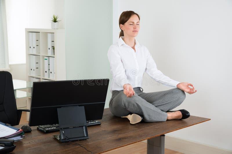 做瑜伽的女实业家在办公室 库存图片